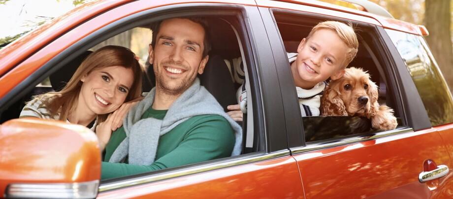 Familie sitzt in rotem Auto mit Ihrem Hund, einem Cockerspaniel und schaut glücklich heraus.